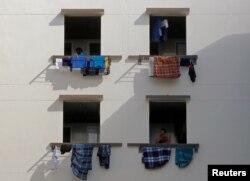 Buruh migran melihat keluar jendela di asrama, di tengah pandemi COVID-19 di Singapura 15 Mei 2020. (REUTERS / Edgar Su)