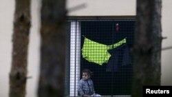 Un niño migrante observa desde la ventana de uno de los centros de detención de extranjeros en Bela-Jezova, República Checa.