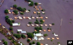 FILE - Only the tops of houses emerge from the water in the city of Santa Fe, Argentina, some 400 kilometers (250 miles) northwest of Buenos Aires, May 1, 2003.
