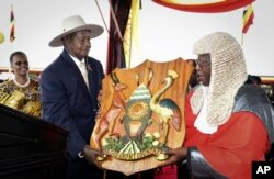 FILE - Uganda's long-time president Yoweri Museveni receives a shield as a symbol of power from the Chief Justice, as his wife Janet Museveni, left, looks on during an inauguration ceremony in the capital Kampala, May 12, 2016.