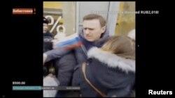 ພາບຢຸດຈາກວີດີໂອ ສະແດງໃຫ້ເຫັນວ່າ ຜູ້ນຳພັກຝ່າຍຄ້ານ ຂອງຣັດເຊຍ ທ່ານອາເລັກເຊ ນາວາລນີ (Alexei Navalny) ກຳລັງຖືກຄວບຄູຸມໂຕ ໂດຍພວກເຈົ້າໜ້າທີ່່ ກະຊວງພາຍໃນ ໃນລະຫວ່າງ ການໂຮມຊຸມນຸມ ເພື່ອພ້ອມໃຈກັນບໍ່ໄປເລືອກຕັ້ງປະທານາທິບໍດີ ເມືອວັນທີ 18 ມີນາ ໃນນະຄອນຫຼາວງ ມົສກູ ຂອງຣັດເຊຍ, ວັນທີ 28 ມັງກອນ 2018.
