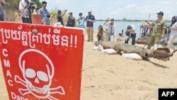Journalists take photograph of a bomb pulled from the murky depths of the Mekong River on Thursday.