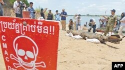 FILE PHOTO - Journalists take photographs of a bomb pulled from the murky depths of the Mekong River, Phnom Penh, Cambodia.