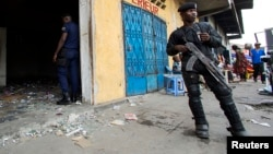 Des policiers déployés devant un magasin à Kinshasa, RDC, 23 janvier 2015.
