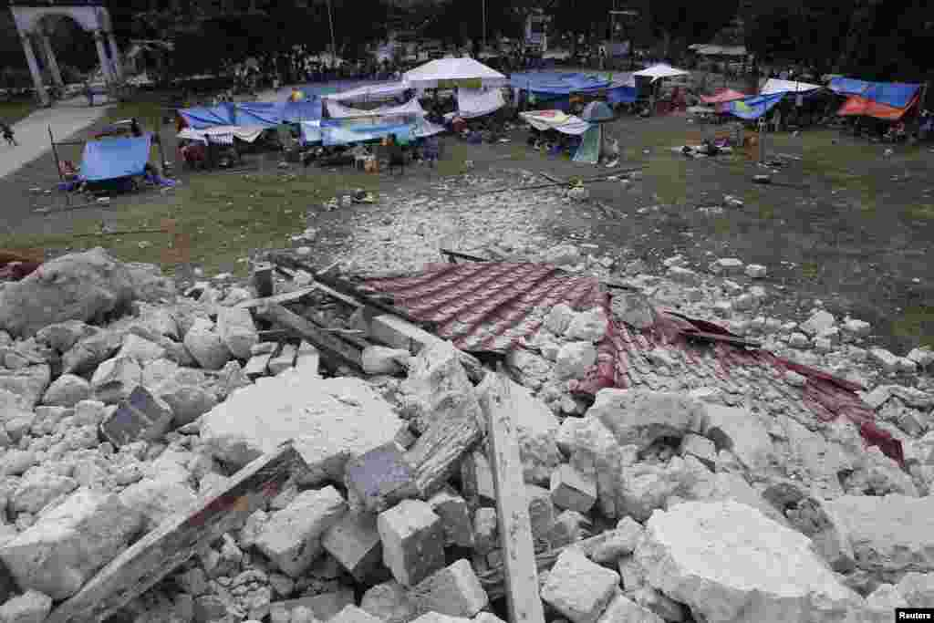 Residents stay in makeshift shelters near the rubble of the centuries-old Our Lady of Light church in Loon, Bohol, a day after an earthquake, Philippines, Oct. 16, 2013.
