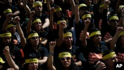 """People protesting against human trafficking and slavery raise their fists during a demonstration in Mexico City, Oct. 14, 2017. Dozens of people participated in Mexico City's silent """"Walk for Freedom."""""""