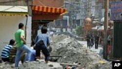 2009年7月8日,维吾尔人看着中国安全部队守在乌鲁木齐维族居住区的入口处