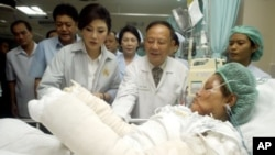 Thailand's Prime Minister Yingluck Shinawatra, third left, visits a victim of Saturday's car bomb attacks at a hospital in Hat Yai Songkhla province, southern Thailand, April 2, 2012.