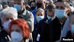 Arhiva - Ljudi noseći zaštitne maske čekaju u redu za vakcinaciju, na Beogradskom sajmu, Beograd, 27. marta 2021. (Foto: AP, Darko Vojinović)