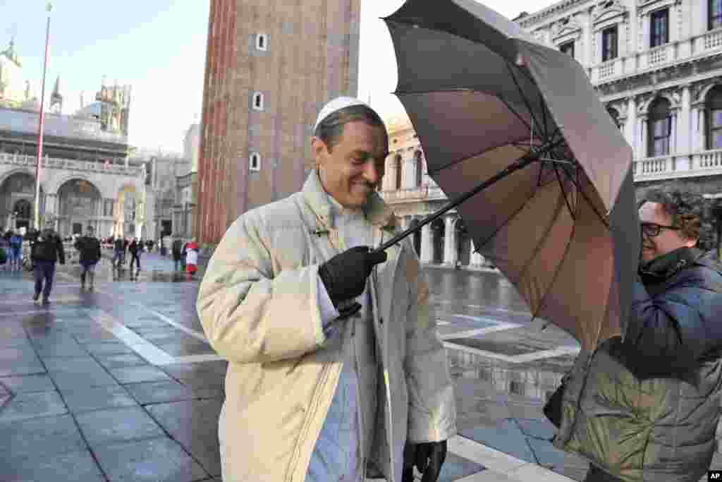 """Nam diễn viên Jude Law cầm dù chặn một nhiếp ảnh gia tại hiện trường của bộ phim truyền hình """"The Young Pope"""" của đạo diễn người Ý Paolo Sorrentino, tại Quảng trường Thánh Mark, thành phố Venice, Ý."""