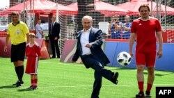 Le président russe Vladimir Poutine, au centre, donne le coup d'envoi à l'ouverture d'un match de football au Parc de la Coupe du monde sur la Place Rouge à Moscou le 28 juin 2018.