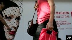 Người phụ nữ đi ngang qua một cửa hàng ở Paris, Pháp. (Ảnh tư liệu)