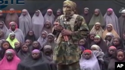FILE - This undated image taken from video distributed Aug. 14, 2016, shows an alleged Boko Haram soldier standing in front of a group of girls alleged to be some of the abducted Chibok schoolgirls held since April 2014.