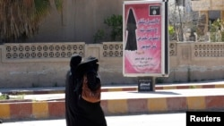 Veiled women walk past a billboard that carries a verse from Koran urging women to wear a hijab in the northern province of Raqqa March 31, 2014.