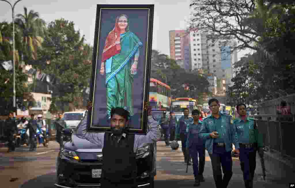 A supporter of Bangladesh Awami League party carries a huge photograph of Prime Minister Sheikh Hasina during an election rally in Dhaka.