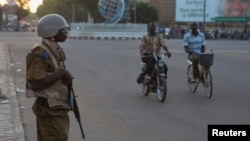 A soldier stands guard outside a building where a meeting between the military and opposition was taking place in Ouagadougou, capital of Burkina Faso, Nov. 2, 2014.