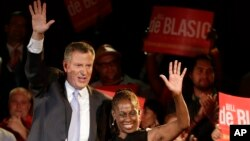 New York City Democratic Mayoral candidate Bill De Blasio, left, and his wife Chirlane wave to supporters at De Blasio election headquarters after polls closed in the city's primary election, Sept. 11, 2013, in New York.