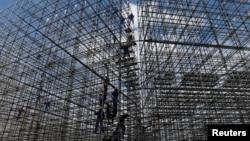 Para pekerja membangun tempat pertandingan olahraga voli pantai untuk olimpiade di pantai Copacabana, Rio de Janeiro, Brazil (foto: dok). Rio de Janeiro disebut sebagai negara bagian yang bangkrut di Brazil.