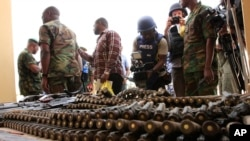 FILE - Journalists look at arms and ammunition which military commanders say they seized from Islamic fighters, in Maiduguri, Nigeria, June 5, 2013.
