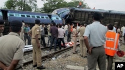 Indian officials and rescuers stand near the wreckage after the Gorakhpur Express passenger train slammed into a parked freight train Chureb, near Basti, Uttar Pradesh state, May 26, 2014.