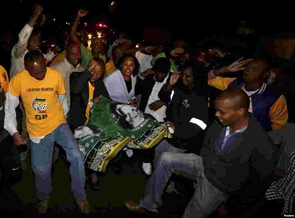 Cư dân tập trung bên ngoài tư gia của cựu Tổng thống Nam Phi Nelson Mandela sau khi được tin ông đã qua đời, ngày 5/12/2013.