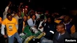 Des Sud-Africains chantant autour de la maison de Nelson Mandela à Johannesburg