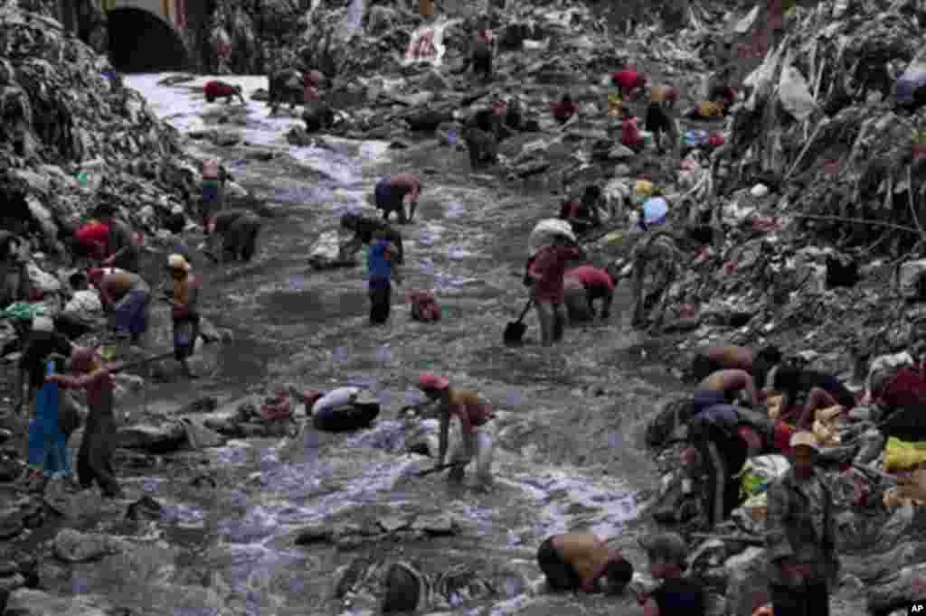 """In this photo taken Wednesday Oct. 19, 2011, people search for scrap metal in contaminated water at the bottom of one of the biggest trash dumps in the city, known as """"The Mine,"""" in Guatemala City. Hundreds of informal workers descend daily into the moun"""