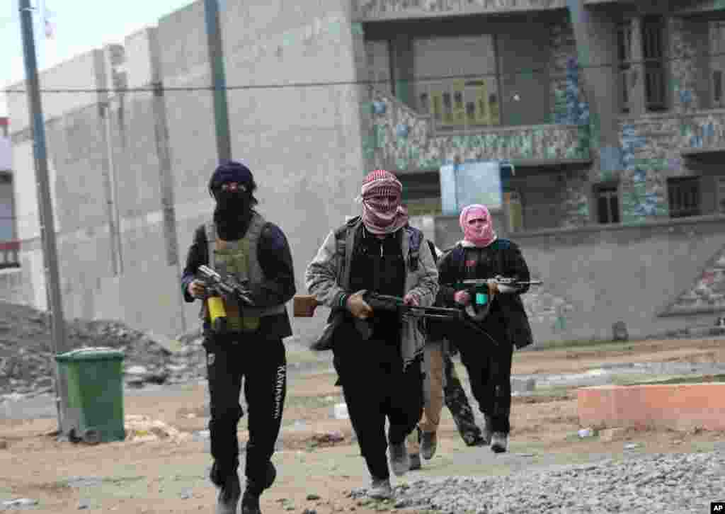 Gunmen patrol during clashes with Iraqi security forces in Fallujah, Jan. 5, 2014.