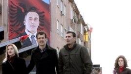 Građani Kosova prolaze pored velikog postera sa likom bivšeg komandanta OVK-a i bivšeg premijera Kosova Ramuš Haradinaj