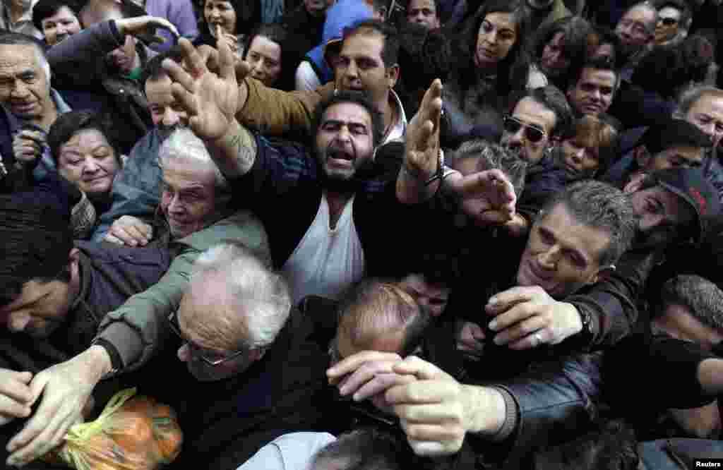 Grci, građani Atine, pokušavaju se domoći besplatnog voća i povrća koje su, u znak protesta protiv visokih poreza i troškova proizvodnje, farmeri dijelili ispred Ministarstva poljoprivrede.