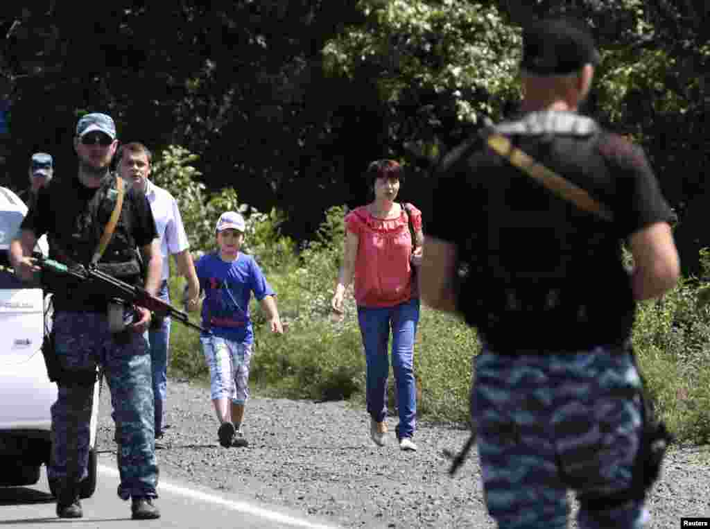 Local residents walk past armed pro-Russian separatists as they flee from what they say was shelling by Ukrainian forces, in the suburbs of Shakhtarsk, Donetsk region, July 28, 2014.