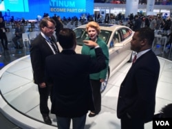U.S. Senator Gary Peters, U.S. Senator Debbie Stabenow, and Assistant Secretary of Commerce for Industry and Analysis Marcus Jadotte tour the Ford exhibit during the first press day at the 2016 North American International Auto Show in Detroit. (K. Farabaugh/VOA)