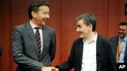 Menteri Keuangan Uni Eropa Jeroen Dijsselbloem (kiri) berjabat tangan dengan Menkeu Yunani, Euclid Tsakalotos dalam pertemuan di Brussels, Belgia (foto: dok).