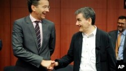 FILE - Dutch Finance Minister and chairman of the eurogroup Jeroen Dijsselbloem, left, shakes hands with Greek Finance Minister Euclid Tsakalotos during a meeting of eurozone finance ministers at the EU Council building in Brussels, Aug. 14, 2015.