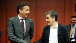 Ketua Eurogroup Jeroen Dijsselbloem (kiri) bersalaman dengan Menkeu Yunani Euclid Tsakalotos dalam pertemuan di Brussels, Jumat (14/8).