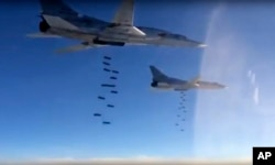 FILE - In this photo made from video released from Russian Defense Ministry official website on Friday, Nov. 20, 2015, Russian air force Tu-22M3 bombers drop bombs on a target in Syria.