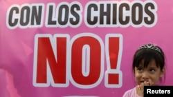 """Une enfant se tient à côté d'une affiche avec l'inscription: """"Touche pas aux enfants!"""" lors d'une manifestation contre les abus et la violence envers les enfants à Lima, au Pérou, le 8 février 2018."""