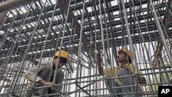 Laborers work at a flyover construction site in Mumbai, 29 Dec 2010