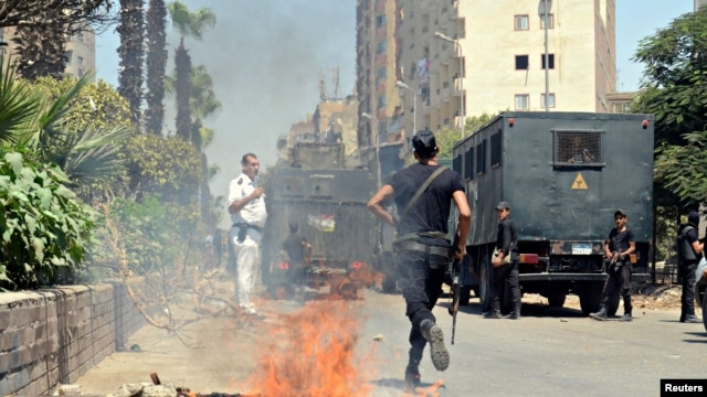 Police take positions after a protest was dispersed quickly, leaving fire burning in a main street in Giza, south of Cairo, August 14, 2014.
