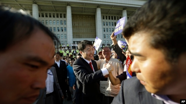 South Korean lawmaker Lee Seok-ki of the leftist Unified Progressive Party, center, is greeted by his supporters as he leaves the National Assembly in Seoul, South Korea, Sept. 4, 2013.