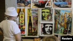 FILE -Tourists look at artwork based on images of revolutionary leader Che Guevara at an artisans' fair in Havana.