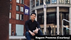 Nagorn Promma sits on the steps in front of NYU Stern School of Business.