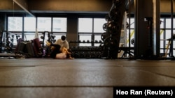 Gym member exercises at a fitness club in Seoul, South Korea, July 12, 2021. Kang Hyun-ku, a gym owner, questioned how it will be possible to control the music people listen to when they wear personal listening devices like earphones. (REUTERS/Heo Ran)