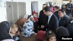 Syria's President Bashar al-Assad (C) speaks with women during his visit to displaced Syrians in the town of Adra in the Damascus countryside March 12, 2014, in this handout photograph released by Syria's national news agency SANA.