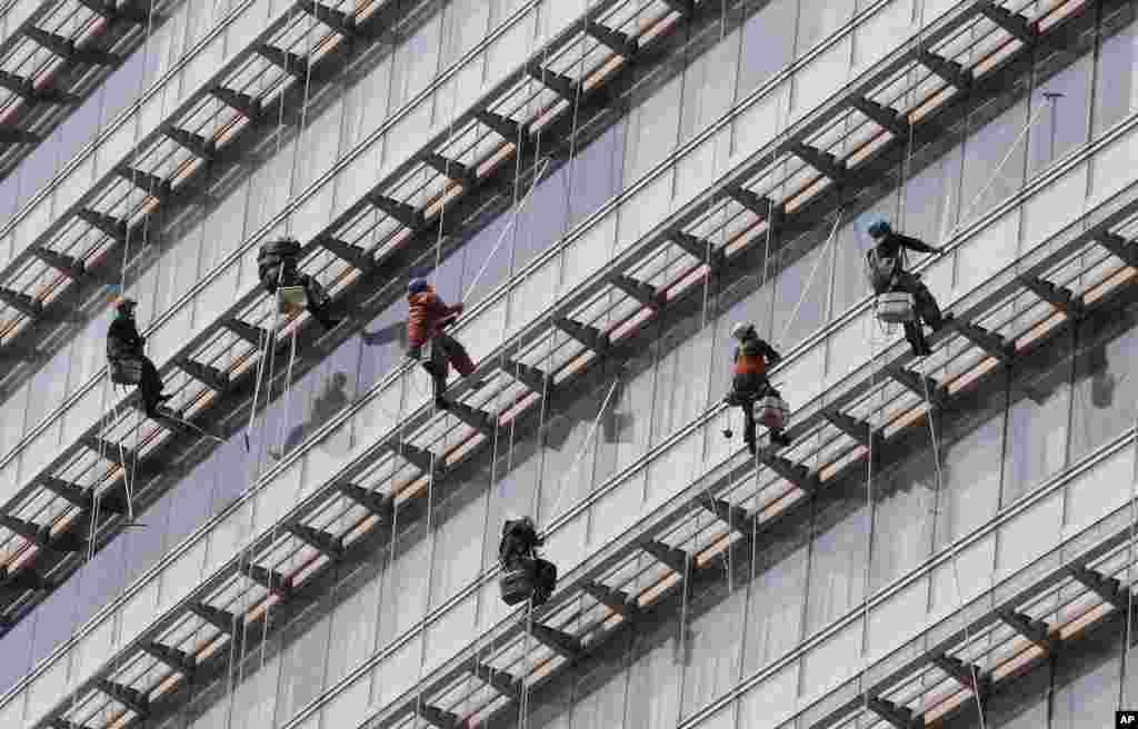 Workers clean windows of an office building in Seoul, South Korea.