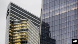 FILE - Goldman Sachs world headquarters, left, neighbors One World Trade Center, in New York, Oct. 28, 2015.