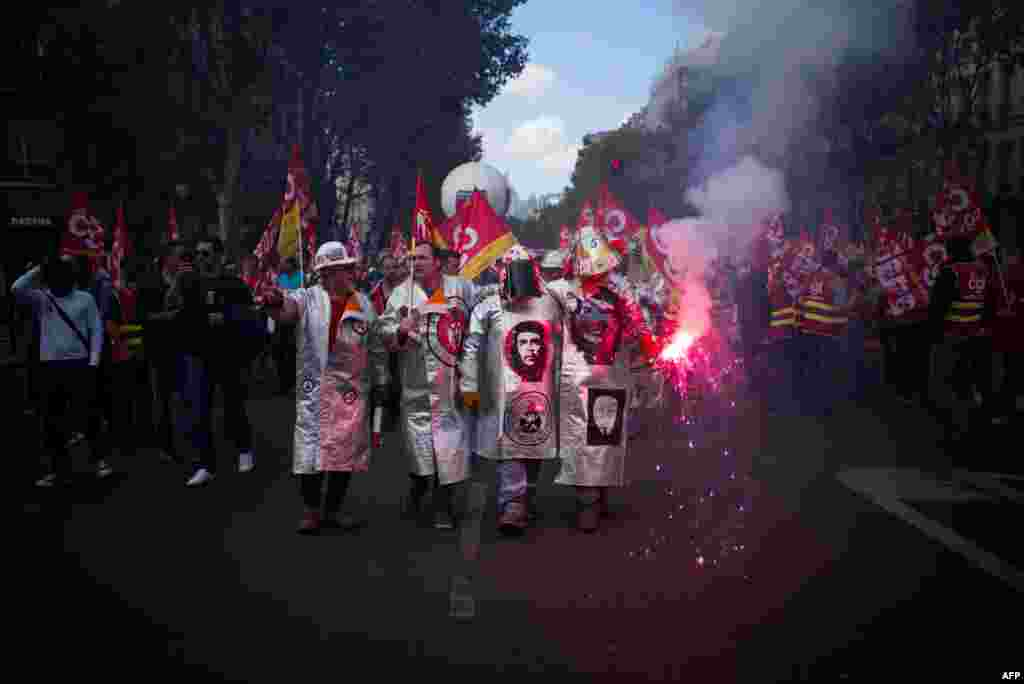 French metalworkers demonstrate as they march with flares, banners and flags in the streets of Paris.