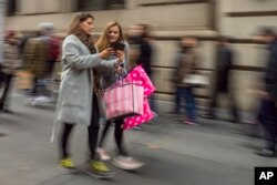Shoppers carry their purchases as they walk along Fifth Avenue on Black Friday in New York, Nov. 25, 2016.