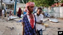 A Somali helps an injured civilian who was wounded in a bomb blast near the Sahafi hotel in the capital Mogadishu, Somalia, Nov. 9, 2018.