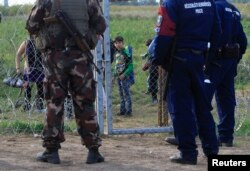 FILE - A migrant child looks at Hungarian policemen and soldier in Roszke, Hungary, Sept. 15, 2015. Hungarian police detained 16 people claiming to be Syrian and Afghan migrants for illegally crossing the Serbian border fence, a police spokeswoman said.